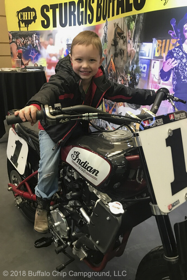A young show attendee smiles atop the Indian FTR750 in the Sturgis Buffalo Chip display