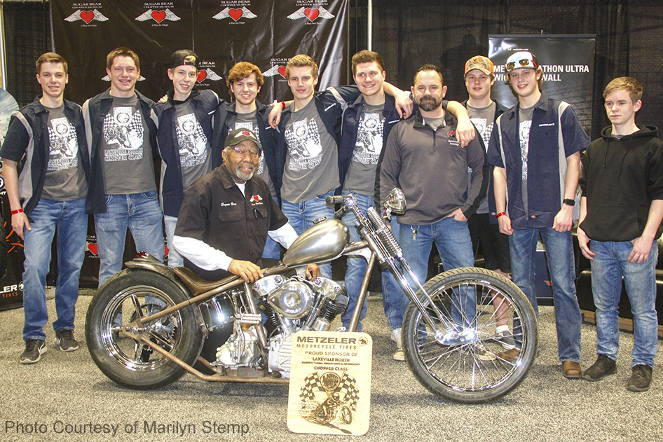 """Sugar Bear, Kevin """"Teach"""" Baas, and a group of Lakeville North High School students pose with the chopper the students are building that features a Sugar Bear Choppers front end."""