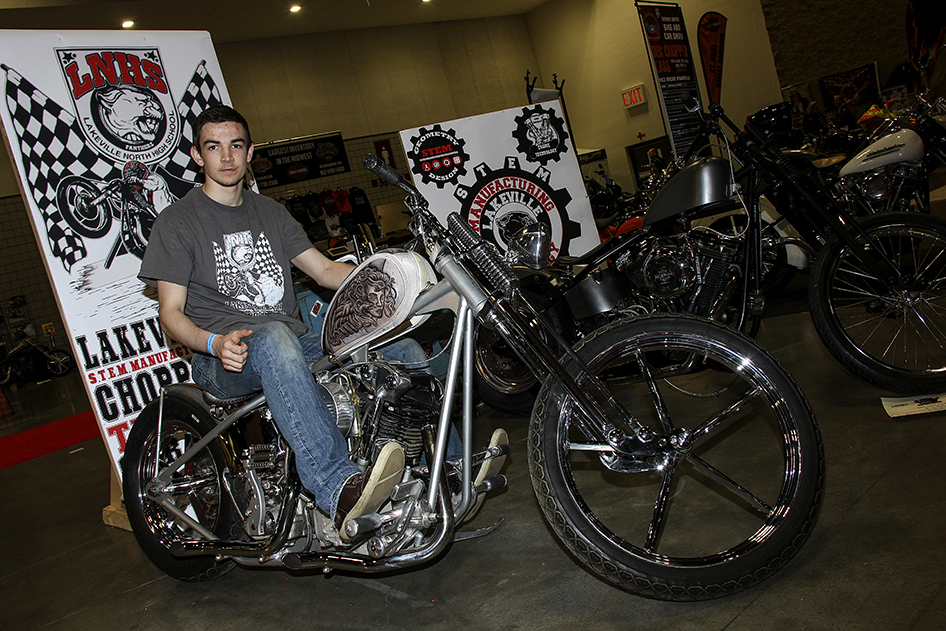 Lakeville High School Chopper Class student poses on top of Chopper Zeus